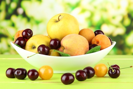 fructose: Bright summer fruits in plate on wooden table on natural background Stock Photo