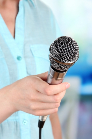 Female with microphone on room background photo