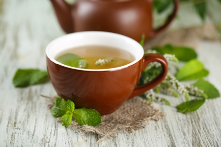 Cup of herbal tea with fresh mint flowers on wooden table photo
