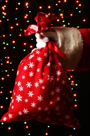 Santa Claus hand holding bag of gifts on bright background