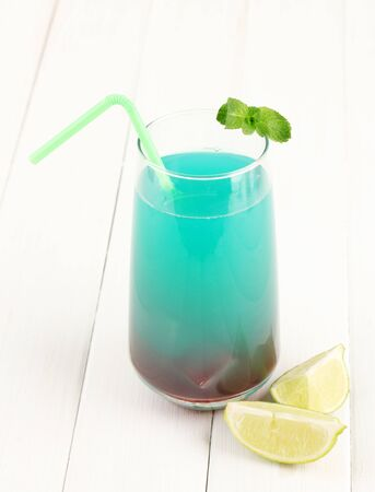 Glass of multicolor cocktail on white background photo