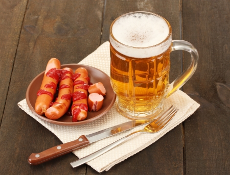 Beer and grilled sausages on wooden background photo