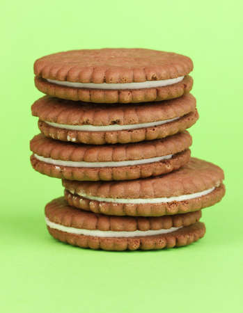 nutritiously: Chocolate cookies with creamy layer on green background Stock Photo