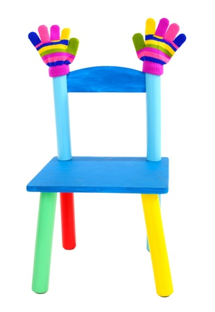 Small and colorful chair with baby mittens isolated on white Stock Photo - 21033219