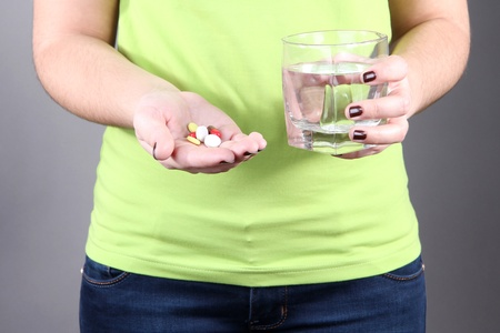 Many pills and glass water in hand photo