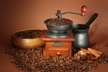 Coffee grinder, turk and coffee beans on brown background photo