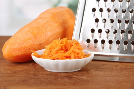 Metal grater and carrot, on bright background photo