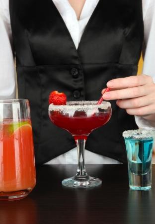 Barmen making tasty cocktails, on bright background photo