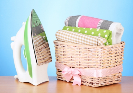 Steam iron and wicker basket with clothes, on color background photo