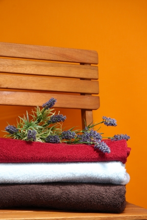 orange washcloth: Towels and flowers on wooden chair on orange background
