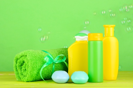 Baby cosmetics, towel and soap on wooden table, on green background photo