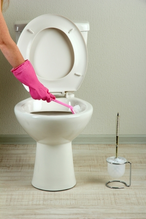Woman hand with brush cleaning a toilet bowl in a bathroom photo