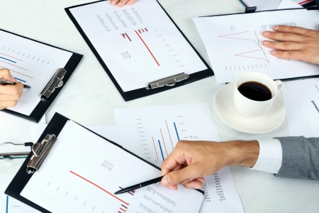 businesspartners: businesspartners hands during discussion of papers close up Stock Photo