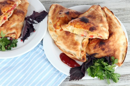 Pizza calzones on plates on napkin on wooden table photo