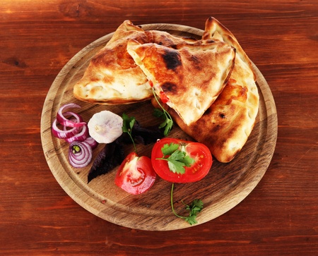 Pizza calzones on wooden board on wooden table photo