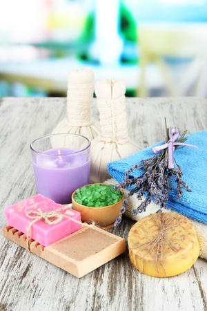Still life with lavender candle, soap, massage balls, bottles,  soap and fresh lavender, on wooden  table on bright background photo