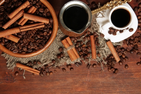 Coffee beans, metal turk and coffee mill on wooden background with copy space photo