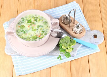 Cabbage soup in plate on napkin on board for cutting on wooden table photo