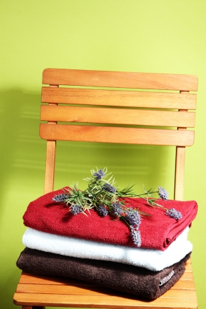 Towels and flowers on wooden chair on green background photo