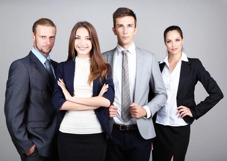 Business team debout dans la rangée sur fond gris