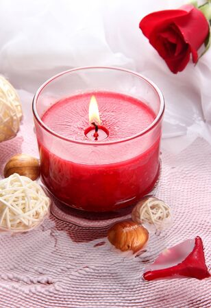 Beautiful red candle with flower petals in water photo