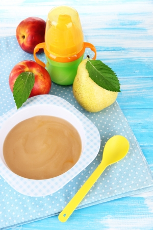 Tasty baby fruit puree and baby bottle on wooden table photo