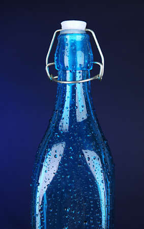 saturated color: Colorful bottle on dark blue background