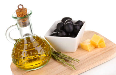 Black olives in white bowl with rosemary,olive oil and cheese on board isolated on white photo