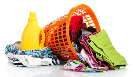 Clothes with detergent and in green plastic basket dropped isolated on white photo