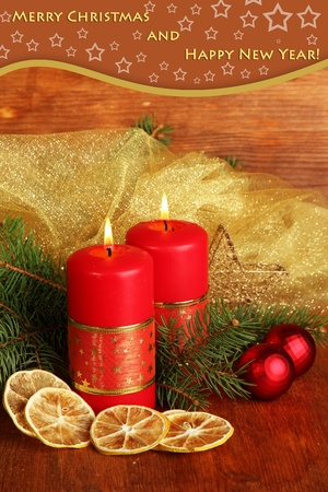 Two candles and Christmas decorations, on wooden background photo