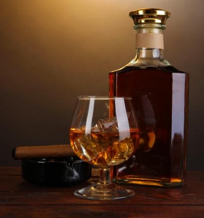 botella de whisky: Brandy con hielo en la mesa de madera sobre fondo marrón