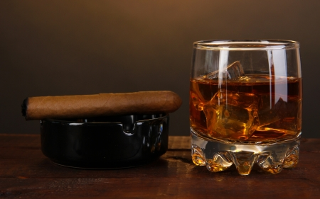 Brandy glass with ice and cigar on wooden table on brown background photo