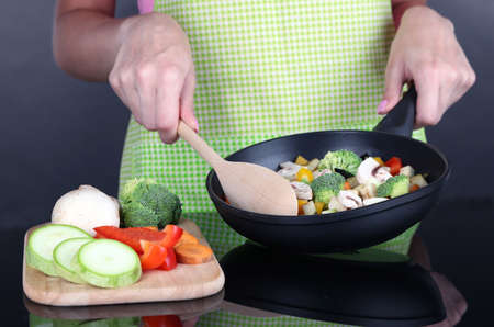 Hands cooking vegetable ragout in pan on gray background photo
