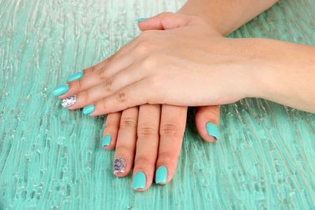 Beautiful woman hands with blue manicure, on color background