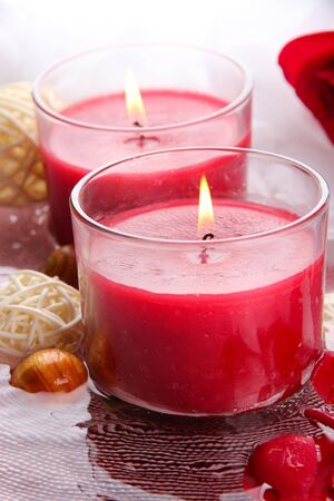 Beautiful red candles with flower petals in water photo