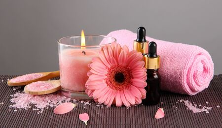Beautiful pink candle with flower and towel on bamboo mat photo