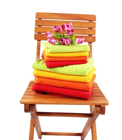 orange washcloth: Towels and flowers on wooden chair isolated on white