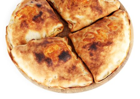 Pizza calzones on wooden board isolated on white photo