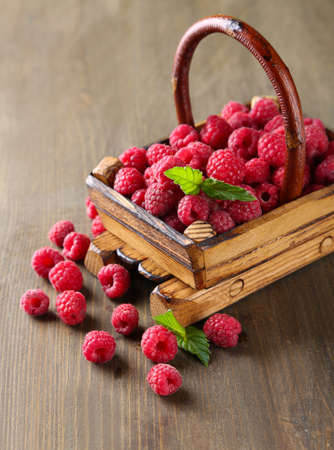 Ripe sweet raspberries in basket on wooden background photo