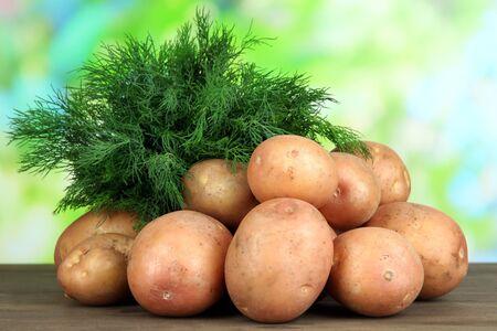 Potato on wooden table photo