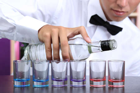 vodka: Bartender is pouring  vodka into glasses Stock Photo