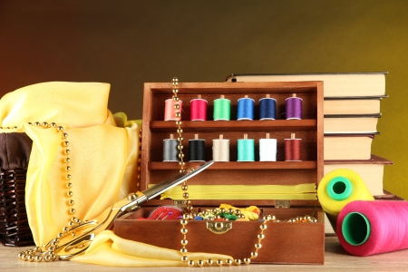 Sewing kit in wooden box with books and cloth table on bright background photo