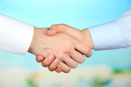 negotiating: Business handshake on bright background