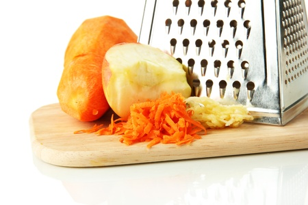 Metal grater and apple, carrot on cutting board, isolated on white photo