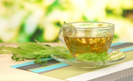 Glass cup of tea with linden on napkin on wooden table on natural background photo