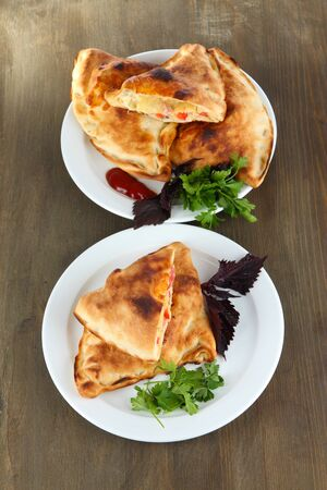 Pizza calzones on plates on wooden table photo