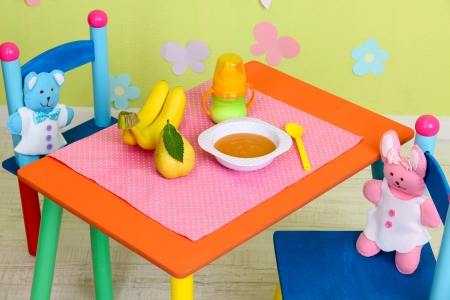 Tasty baby fruit puree and baby bottle on table in room photo