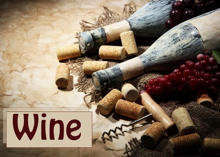 Old bottles of wine, grapes and corks on old paper background photo