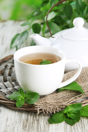 Teapot and cup of herbal tea with fresh mint on wooden table photo