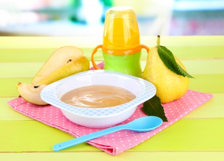 Tasty baby fruit puree and baby bottle on wooden table Stock Photo - 21245663